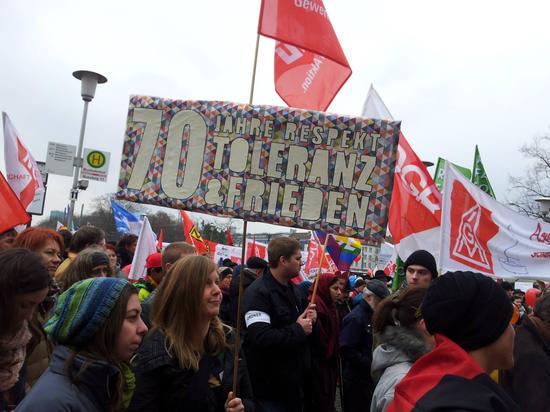 """Im Demonstrationszug waren neben bunten Luftballons, Fahnen und Transparenten viele selbstgestaltete Plakate zu sehen. Die IG Metall Kolleginnen und Kollegen von Bavaria Yachtbau waren mit einem Transparent vor Ort, auf dem zu lesen war """"Asylbewerbern einen sicheren Hafen bieten. Die junge IG BAU gestaltete ein Plakat mit der Aufschrift. """"70 Jahre Toleranz, Respekt und Frieden"""". Die DGB Hochschulgruppe war mit einem roten Transparent dabei: """"DGB Jugend Würzburg gegen Ausländerfeindlichkeit""""."""