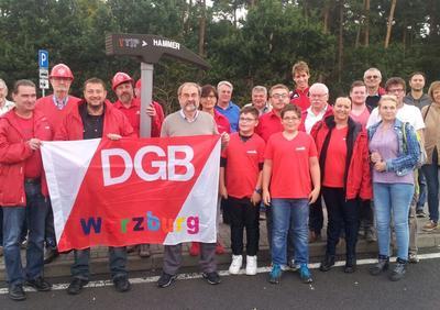 Drei DGB Busse aus Würzburg waren am Samstag nach Frankfurt zur Stopp TTIP Demo unterwegs. Beim kurzen Zwischenstopp in Weisskirchen: Gruppenfoto der Würzburger Bauleute mit dem Stopp TTIP Demo Hammer. 10 vom DGB organisierte Busse aus Unterfranken waren in Summe unterwegs.