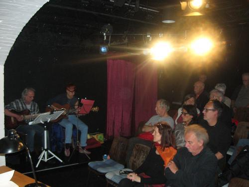 """Den Vortrag ergänzten Sonja Stöcklein und Peter Schüllermann. Mit ihren musikalischen Beiträgen wurde die Zeitreise durch das Leben des Konrad Försch lebendig. Abgestimmt auf die jeweiligen Lebensabschnitte waren es das Lied """"Giftgas"""" (Rote Raketen 1926), das """"Einheitsfrontlied"""" (Brecht/Eisler), eine Interpretation von """"Hakenrune"""" (Weinert), die """"Kinderhymne"""" (Eisler) und die Eigenkomposition """"100 Jahre Metaller"""", die am Ende des Abends den Bezug zur Gegenwart herstellte und hart mit der politischen Verschärfung der Asylgesetzgebung ins Gericht ging."""